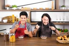 Hübsche junge Männer, die Frühstück, einen Mannhandzeichendaumen oben und den anderen in der modernen Esszimmerwohnung zu löffeln stockbilder