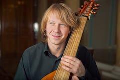Hübsche junge Musikerspielbassgeige im Palast lizenzfreies stockfoto