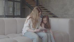 Hübsche junge Mutter des Porträts und ihre nette kleine Tochter verwenden eine Tablette und ein Lächeln und sitzen auf Sofa im gr stock video footage