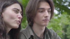 Hübsche junge Paare des Porträts in der zufälligen Kleidung, die zusammen Zeit im Park, ein Datum habend verbringt Der Kerl, der  stock video footage