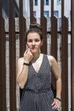 Hübsche junge stilvolle Frauenstellung gegen einen Zaun lizenzfreies stockbild