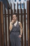 Hübsche junge stilvolle Frauenstellung gegen einen Zaun lizenzfreie stockfotografie