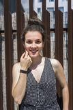 Hübsche junge stilvolle Frauenstellung gegen einen Zaun stockfoto
