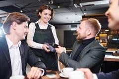Hübsche Kellnerin, die Anschluss für Zahlung an Geschäftsmann gibt stockbild