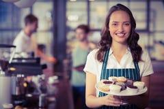 Hübsche Kellnerin, die eine Platte von kleinen Kuchen zeigt Lizenzfreies Stockbild