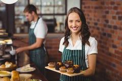 Hübsche Kellnerin, die einen Behälter von Muffins hält Stockfotos