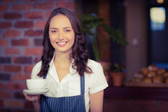 Hübsche Kellnerin, die einen Tasse Kaffee hält Lizenzfreies Stockbild