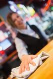 Hübsche Kellnerin, die hinunter Stange abwischt Stockfoto