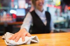 Hübsche Kellnerin, die hinunter Stange abwischt Stockfotografie