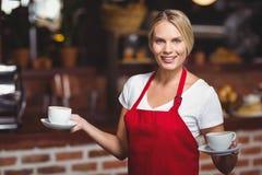 Hübsche Kellnerin, die zwei Schalen Kaffee hält Stockfotos