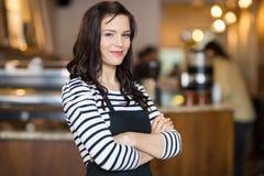 Hübsche Kellnerin Standing Arms Crossed in der Cafeteria Lizenzfreie Stockfotos