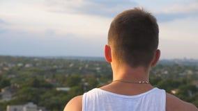Hübsche Kerlstellung am Rand der Dachspitze und der rauchenden Zigarette mit unscharfem Stadtbildhintergrund Stillstehen des jung stock footage
