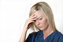 Hübsche Krankenschwester mit Druckkopfschmerzen lizenzfreie stockfotografie