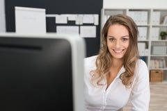 Hübsche lächelnde Büro-Frau, welche die Kamera betrachtet Lizenzfreie Stockfotografie