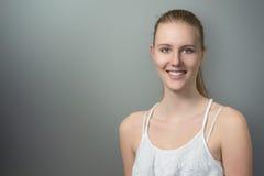 Hübsche lächelnde Frau auf Grau mit Kopien-Raum Lizenzfreies Stockbild