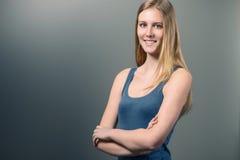 Hübsche lächelnde Frau auf Grau mit Kopien-Raum Lizenzfreie Stockfotos
