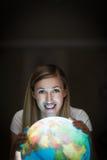 Hübsche lächelnde Frau bei der Anwendung einer Erdkugel Lizenzfreies Stockfoto