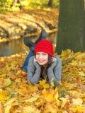 Hübsche lächelnde Frau, die auf Autumn Leaves liegt Lizenzfreie Stockfotos