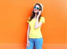 Hübsche lächelnde Frau, die auf Smartphone über bunter Orange spricht stockfotografie