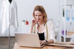 Hübsche lächelnde Frau, die an Laptop arbeitet Stockbild