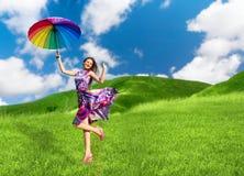 Hübsche lächelnde Frau mit buntem Regenschirm Stockfotos