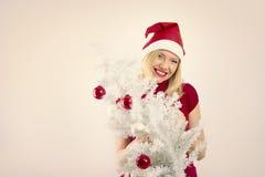 Hübsche lächelnde Frau mit Weihnachtsbaum Stockfoto