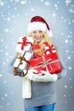 Hübsche lächelnde Frau mit Weihnachtsgeschenk Lizenzfreie Stockbilder