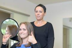 Hübsche lächelnde Frau 20s an den Friseuren Stockbild