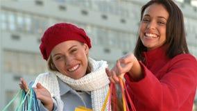 Hübsche lächelnde Mädchen, die Einkaufstaschen zeigen stock video footage