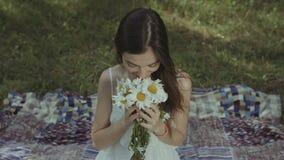 Hübsche lächelnde riechende Kamille der Frau im Park stock video footage