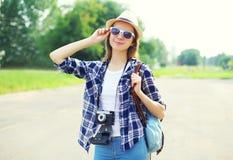 Hübsche lächelnde tragende Strohhutsonnenbrille der Frau und Weinlesekamera Lizenzfreies Stockfoto