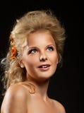 Hübsche Lächelnfrau mit Blume im Haar Stockfotografie