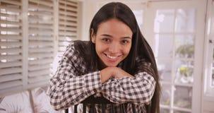 Hübsche Latina-Frau, die zu Hause das Lächeln an der Kamera sitzt stockbilder