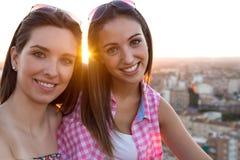 Hübsche Mädchen, die auf dem Dach bei Sonnenuntergang sitzen Lizenzfreie Stockfotos