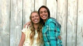 Hübsche Mädchen, die an der Kamera umarmen und lächeln stock video footage