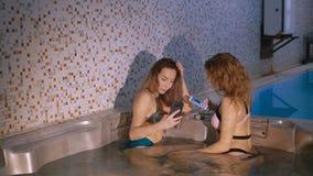 Hübsche Mädchen, die im Jacuzzi stillstehen und Technologie einsetzen 4K stock video