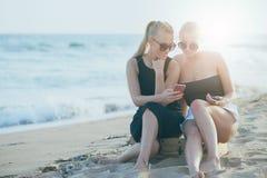 Hübsche Mädchen, die Telefon auf einem sandigen Strand verwenden stockfotos