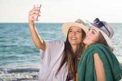 Hübsche Mädchen am Strand, der Selfie nimmt Stockfotografie