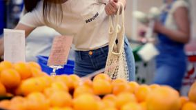 Hübsche Mädchenfrau, die Veggies und Früchte im supernarket in der organischen Einkaufstasche der Masche, nullabfall, eco freundl stock video footage