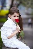 Hübsche Mädchengeruchrose im Freien in der weißen Klage Lizenzfreie Stockfotografie