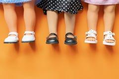 Hübsche Mädchenpuppenbeine, welche die Sandalen und Röcke legen auf orange Hintergrund b tragen stockfotos