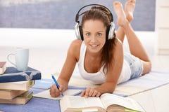Hübsche Mädchenschreibensheimarbeit, die auf Fußboden legt Lizenzfreies Stockbild