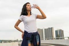 Hübsche malaysische Dame Drinks Water im Freien lizenzfreie stockbilder
