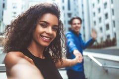 Hübsche Mischrassefrau, die ein selfie in der modernen Stadt nimmt stockfoto