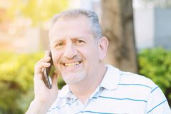 Hübsche Mitte alterte den Mann, der am Telefon spricht Lizenzfreies Stockfoto