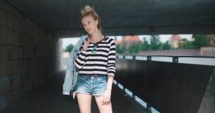 Hübsche Modefrau, die unter einer Brücke, schauend zu einer Kamera und zu einem Lächeln aufwirft stock footage