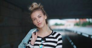 Hübsche Modefrau, die unter einer Brücke, schauend zu einer Kamera und zu einem Lächeln aufwirft stock video footage