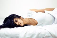 Hübsche Mulatte Brunettefrau im Bett, schräger Schlaf Stockfotografie