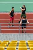 Hübsche multiethnische Athletengruppe machen das Ausdehnen von Übungen stockbild