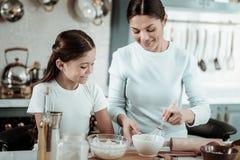Hübsche Mutter, die einen Tag mit einer Tochter in der Küche verbringt lizenzfreie stockfotos